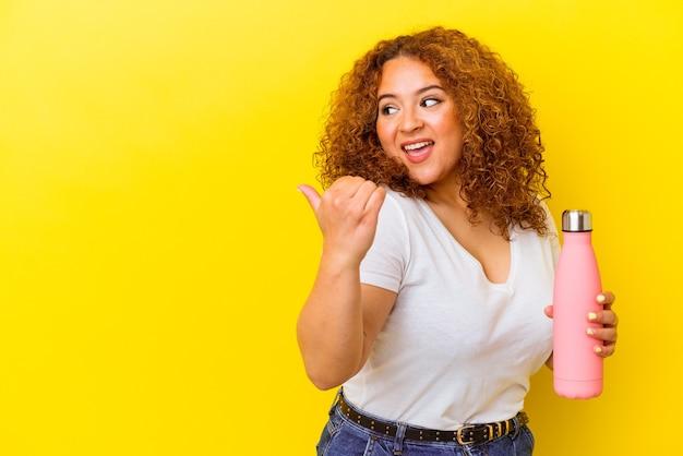 Jeune femme latine tenant un thermos isolé sur des points de mur jaune avec le pouce, riant et insouciant