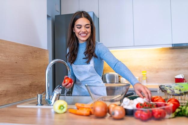 Jeune femme lave les légumes dans la cuisine domestique