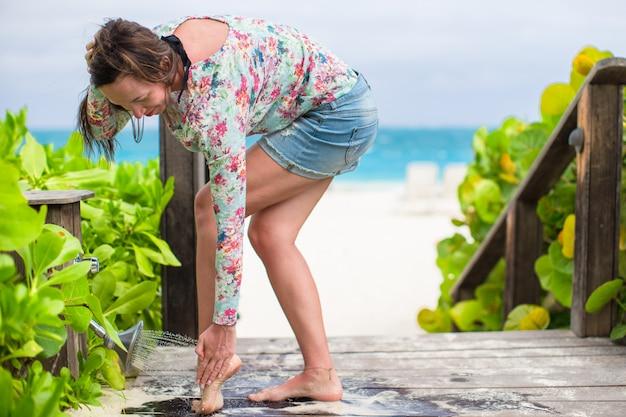 Jeune femme lave le sable de ses pieds sur la plage blanche