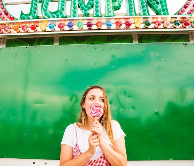 Jeune femme léchant sucette au parc d'attractions