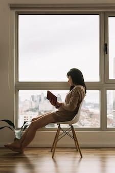 Jeune femme, lecture, près, énorme, fenêtre