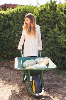 Jeune femme avec des légumes frais dans un chariot