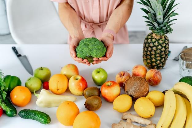 Jeune femme avec des légumes tenant le brocoli dans les mains la cuisson dans la cuisine. table avec des aliments sains. photo recadrée.