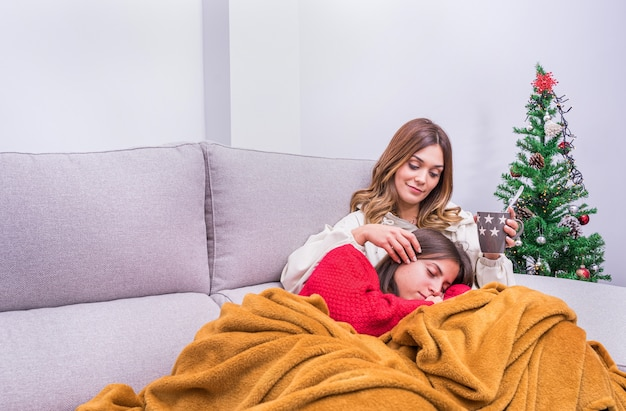 Jeune femme lesbienne buvant du café, pendant qu'elle caresse son partenaire pendant qu'elle dort à côté de l'arbre de noël. concept de couple lgbt, détente et vie à la maison