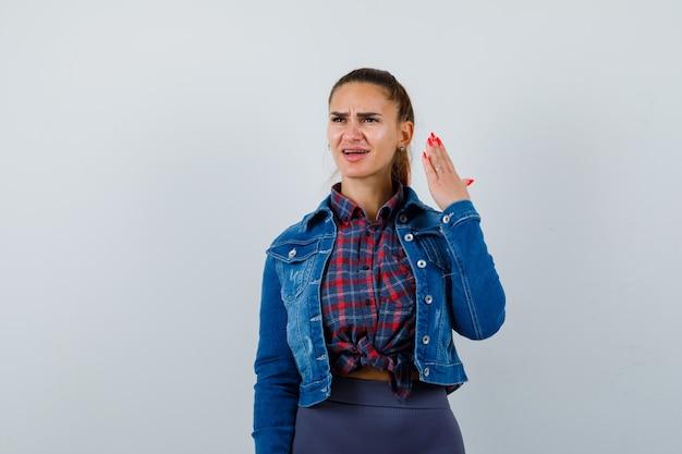 Jeune femme levant la main dans un geste perplexe tout en levant les yeux en chemise, veste et l'air mécontent, vue de face.