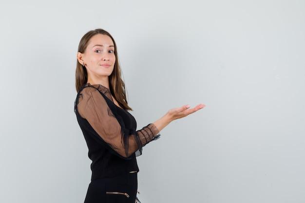 Jeune femme levant la main avec la paume ouverte montrant quelque chose en chemisier noir et à la recherche concentrée. espace pour le texte