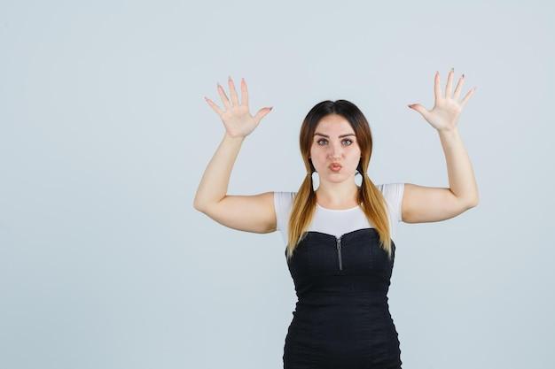 Jeune femme levant les mains au-dessus de la tête tout en boudant les lèvres