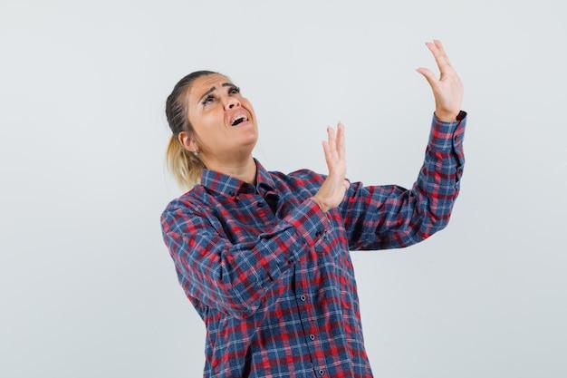 Jeune femme levant les mains comme arrêter quelque chose en chemise à carreaux et à l'air stressé. vue de face.