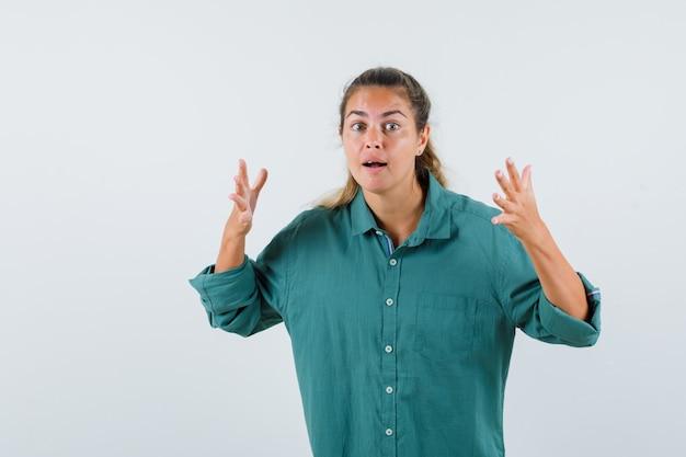 Jeune femme levant les mains de manière interrogative en chemise bleue et à la surprise