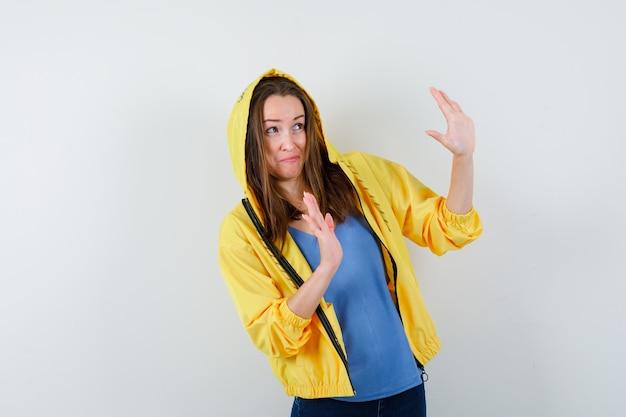 Jeune femme levant les mains de manière protectrice en t-shirt, veste et ayant l'air effrayée, vue de face.