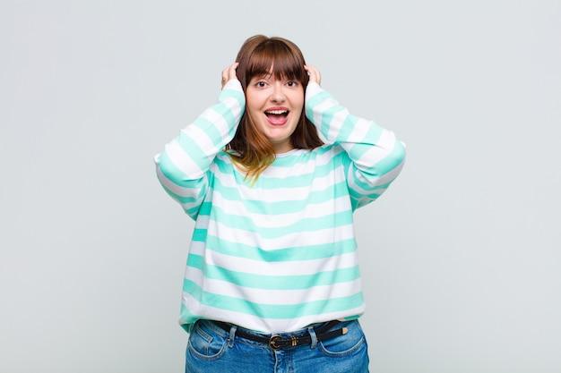 Jeune femme levant les mains à la tête, bouche bée, se sentant extrêmement chanceux, surpris, excité et heureux