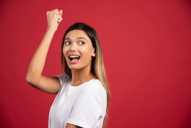 Jeune femme levant son poing sur le mur rouge.