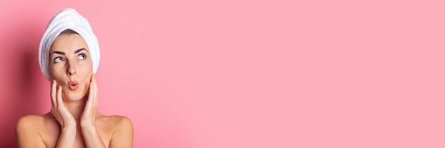 Jeune femme levant la surprise avec une serviette sur la tête sur une bannière de fond rose