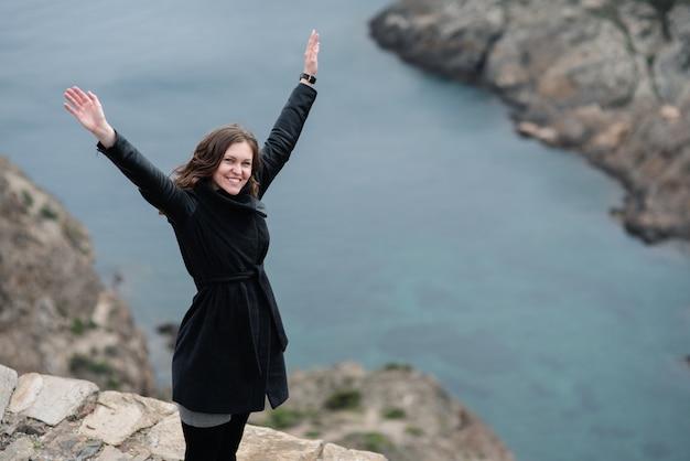 Jeune femme lève les bras vers le ciel en signe de liberté et de succès