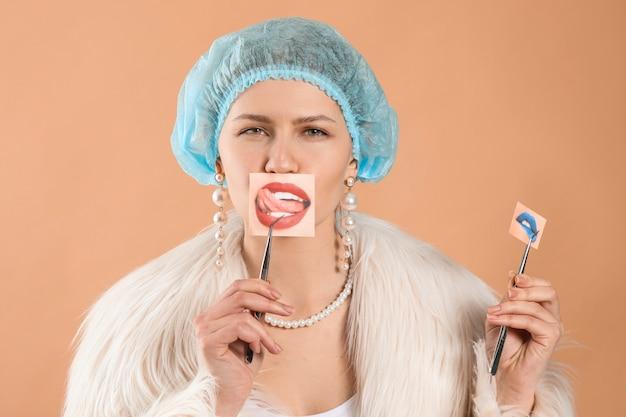 Jeune femme avec des lèvres en papier sur la couleur.