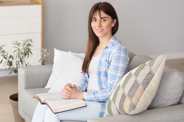 Jeune femme lisant la bible à la maison