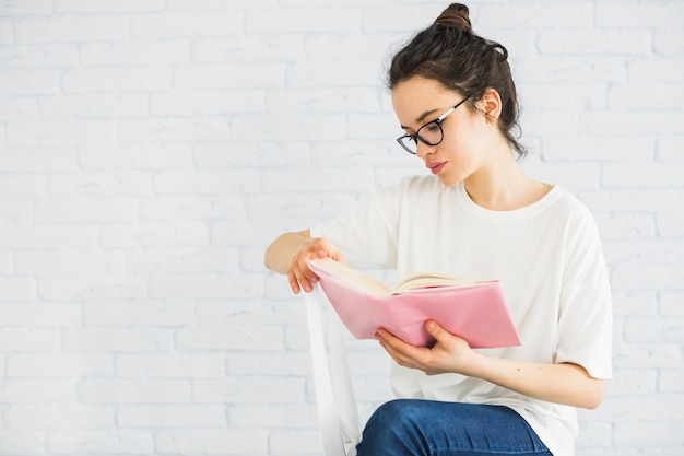 Jeune femme lisant sur une chaise