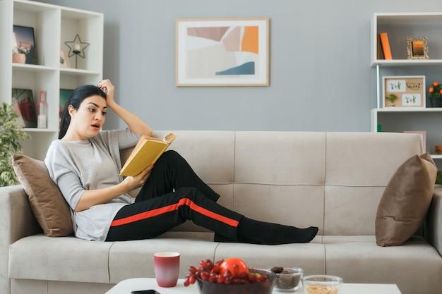 Jeune femme lisant un livre allongé sur un canapé derrière une table basse dans le salon