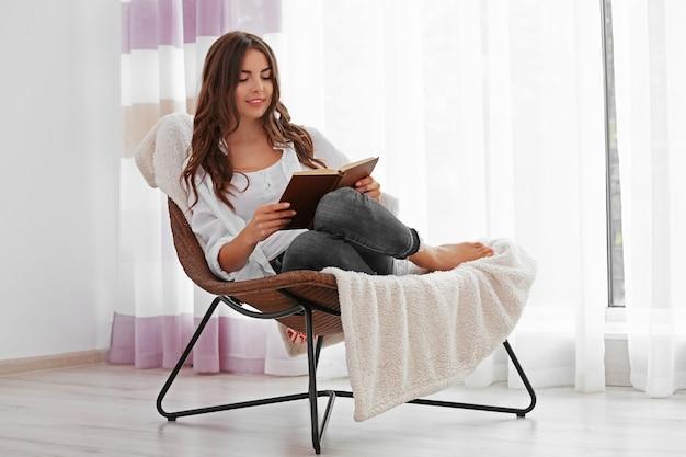 Jeune femme lisant un livre et assis sur une chaise confortable à la maison