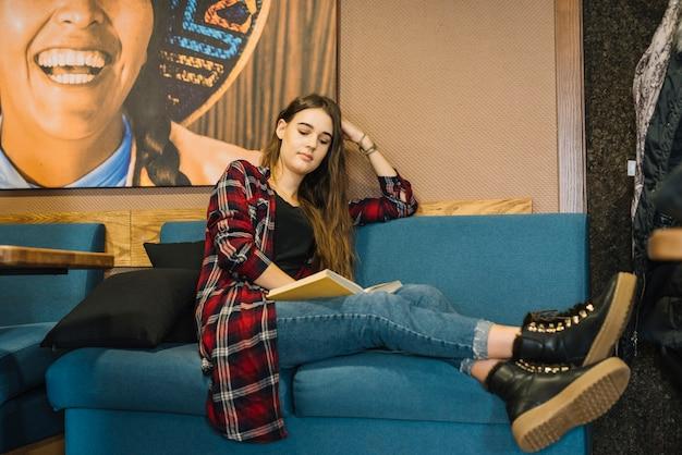 Jeune femme lisant un livre au café