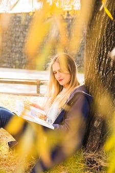 Jeune femme lisant livre automne arbre inclinable