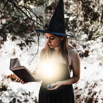 Jeune femme lisant un livre avec une bougie allumée dans les bois