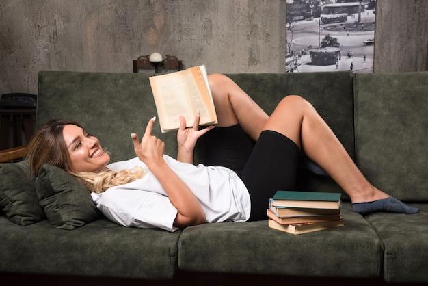 Jeune femme lisant un livre sur le canapé avec une expression heureuse.