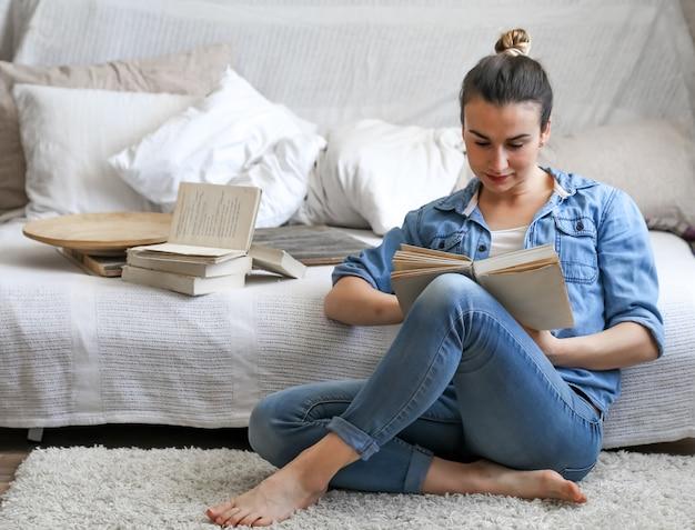 Jeune femme lisant un livre dans une chambre confortable