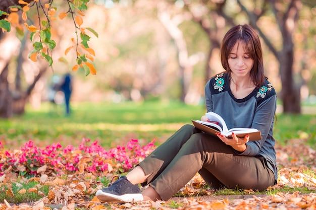 Jeune femme lisant un livre dans le magnifique parc d'automne