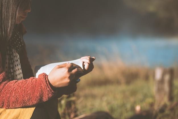 Jeune femme lisant un livre dans le parc naturel avec la fraîcheur du matin