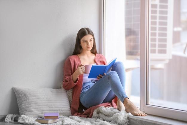 Jeune femme lisant un livre à la maison
