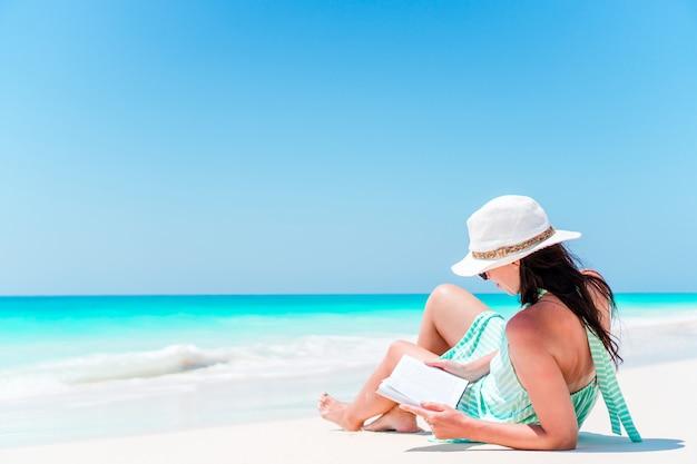 Jeune femme lisant un livre pendant la plage blanche tropicale