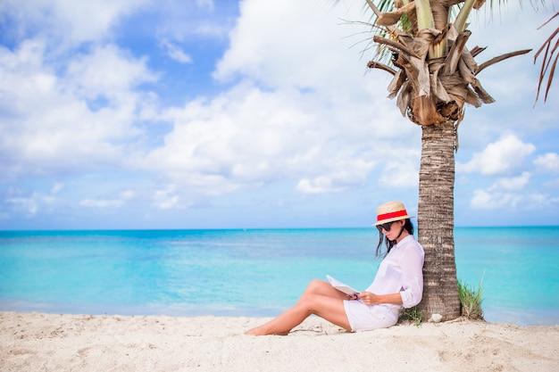 Jeune femme lisant un livre pendant la plage tropicale