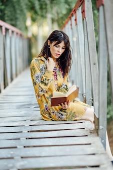 Jeune femme lisant un livre sur un pont rural.