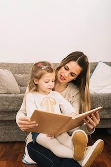 Jeune femme lisant un livre à sa fille près du canapé