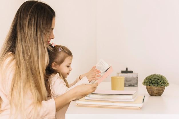 Jeune femme lisant un livre avec sa fille à table