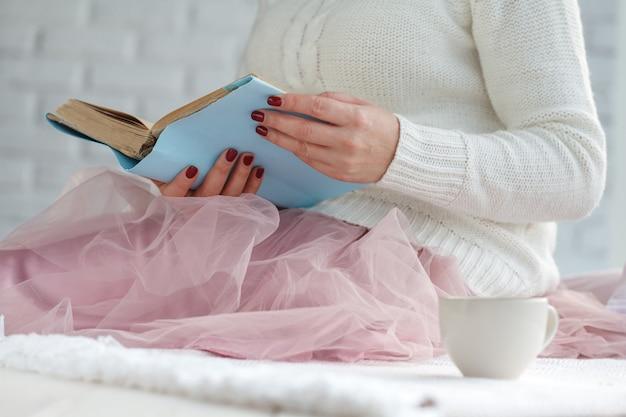 Jeune femme lisant un livre et se prélassant avec plaid et café