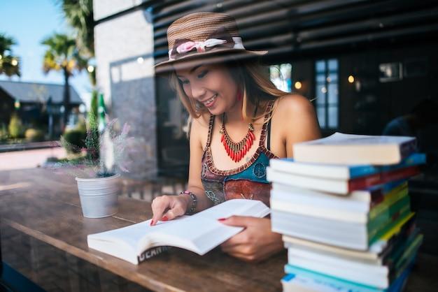 Jeune femme lisant un livre et une tasse de café frais sur la table