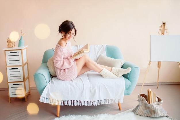 Jeune femme lisant un livre et tenant une tasse de café