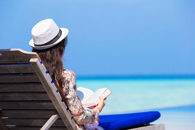 Jeune femme lisant un livre sur les vacances d'été à la plage blanche