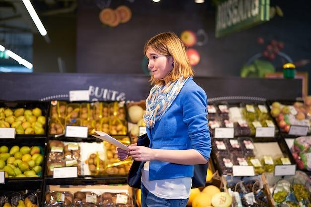 Jeune femme avec une liste de courses en magasin