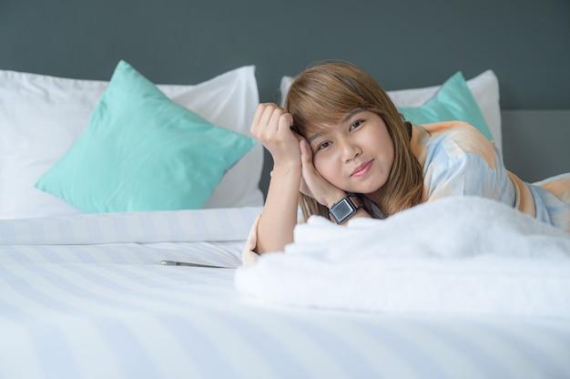 Jeune femme sur lit à l'heure du matin