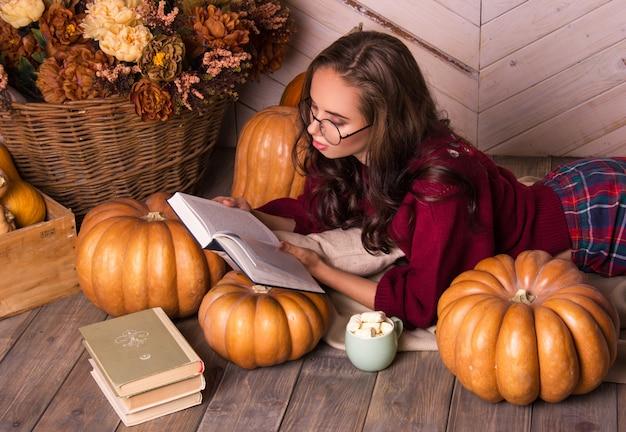 Jeune femme lit un livre à l'intérieur de l'automne avec des citrouilles