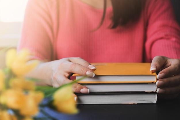 Jeune femme lit un livre à la maison.