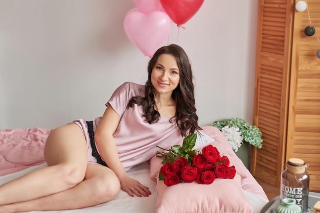 Jeune femme sur lit en pyjama rose avec bouquet de roses rouges