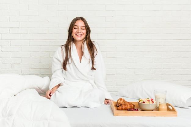 Jeune femme sur le lit rit et ferme les yeux, se sent détendue et heureuse