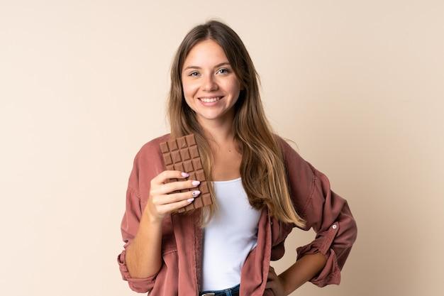 Jeune femme lituanienne isolée sur fond beige en prenant une tablette de chocolat et heureux