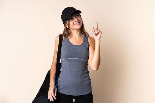 Jeune femme lituanienne de sport tenant un sac de sport isolé sur beige pointant vers le haut une excellente idée