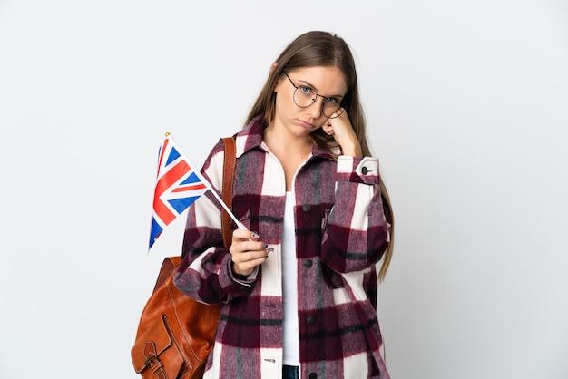 Jeune femme lituanienne tenant un drapeau du royaume-uni isolé sur un mur blanc avec une expression fatiguée et ennuyée