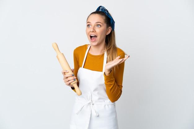Jeune femme lituanienne tenant un rouleau à pâtisserie isolé sur fond blanc avec une expression faciale surprise